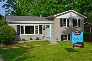 Gray painted brick split level home with black shutters light blue front door and brown and blue Savvy Sign in the front yard