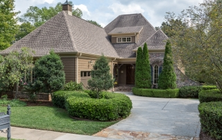 Brown shingle brick and stone two story home with high sloped brown shingle roof brown two car garage door blue shutters manicured trees and bushes