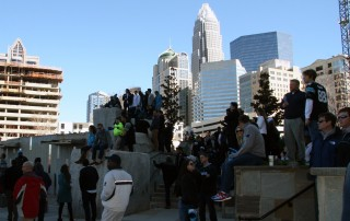 Crowd of people in uptown Charlotte outside Bank of America stadium with skyline behind them