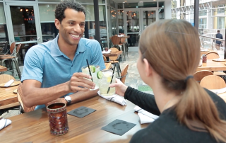 Matthew Means and a women clinking their drinks sitting in an outdoor seating area of a restaurant