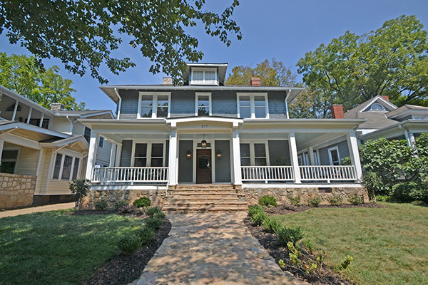 Three story home with gray siding and gray shingles brown front door front porch with white columns and white railing stone detail along bottom