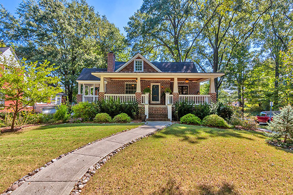 Red brick home with brown shingle details wrap around porch with white columns and railing stone lined cement pathway