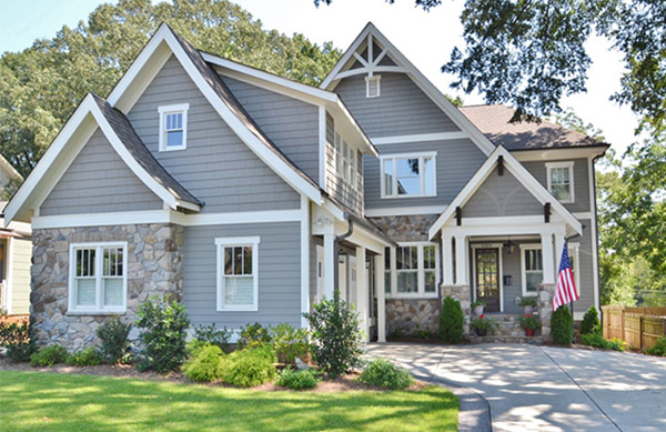 Two story home with gray siding and gray shingles with stone details white trim