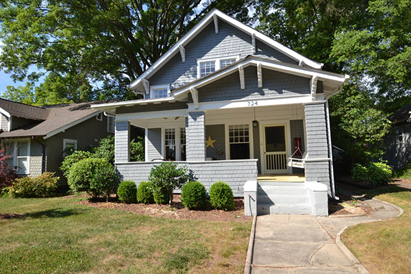 Gray painted brick and shingle home with covered front porch yellow detail on front door