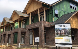 Row off two story townhomes under construction with brick on the first story and dirt in yard