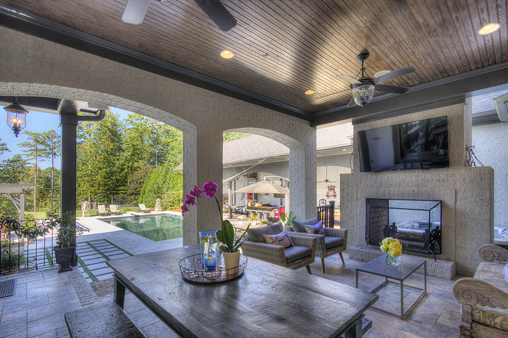 Large covered back patio with dining table sitting are fire place ceiling fans wood and brick covering pool in back ground