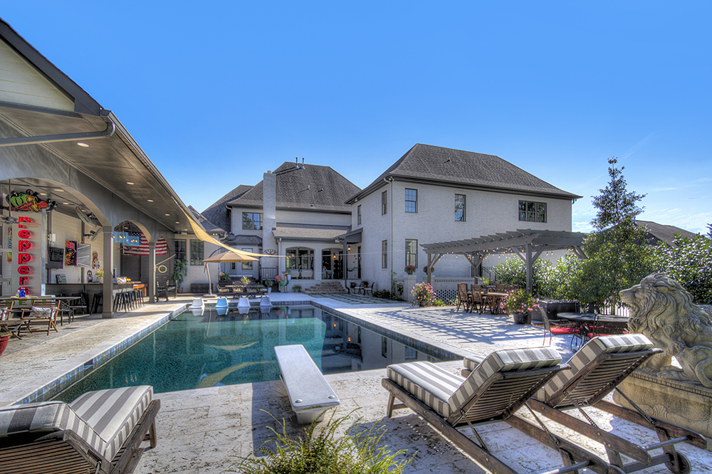 Backyard with built in pool with lounge are covered outdoor dining area lion statue
