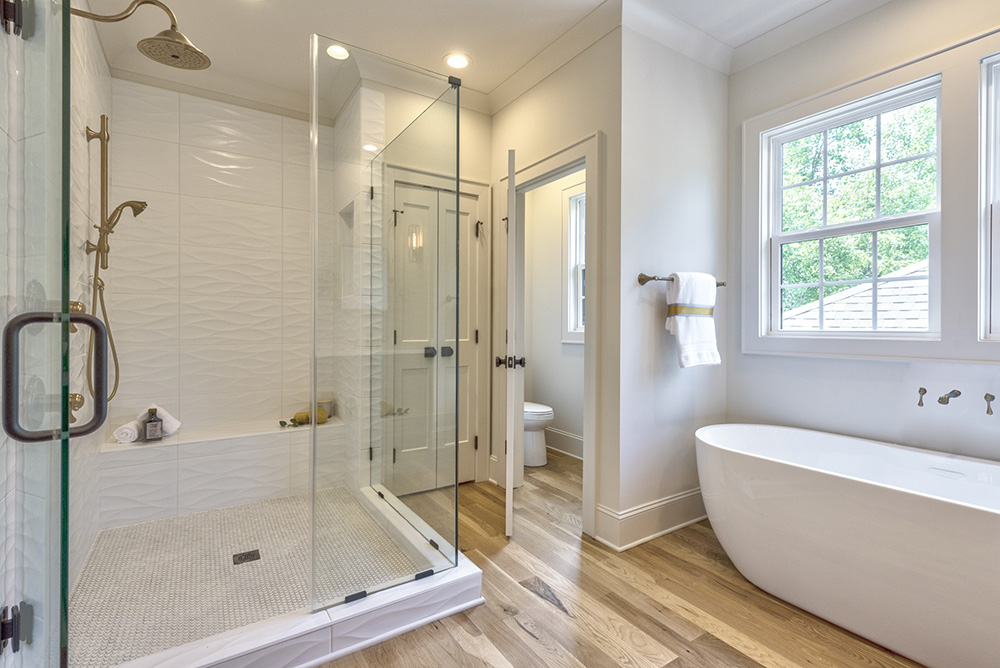 Bathroom with white walls wood floors and white soaking tub with windows over it large walk in white shower with glass doors
