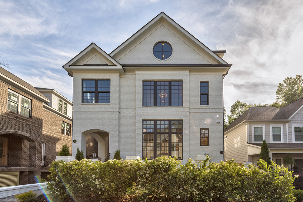Large three story duplex with white brick and brown framed windows and brown shingle roof with archway over front porch