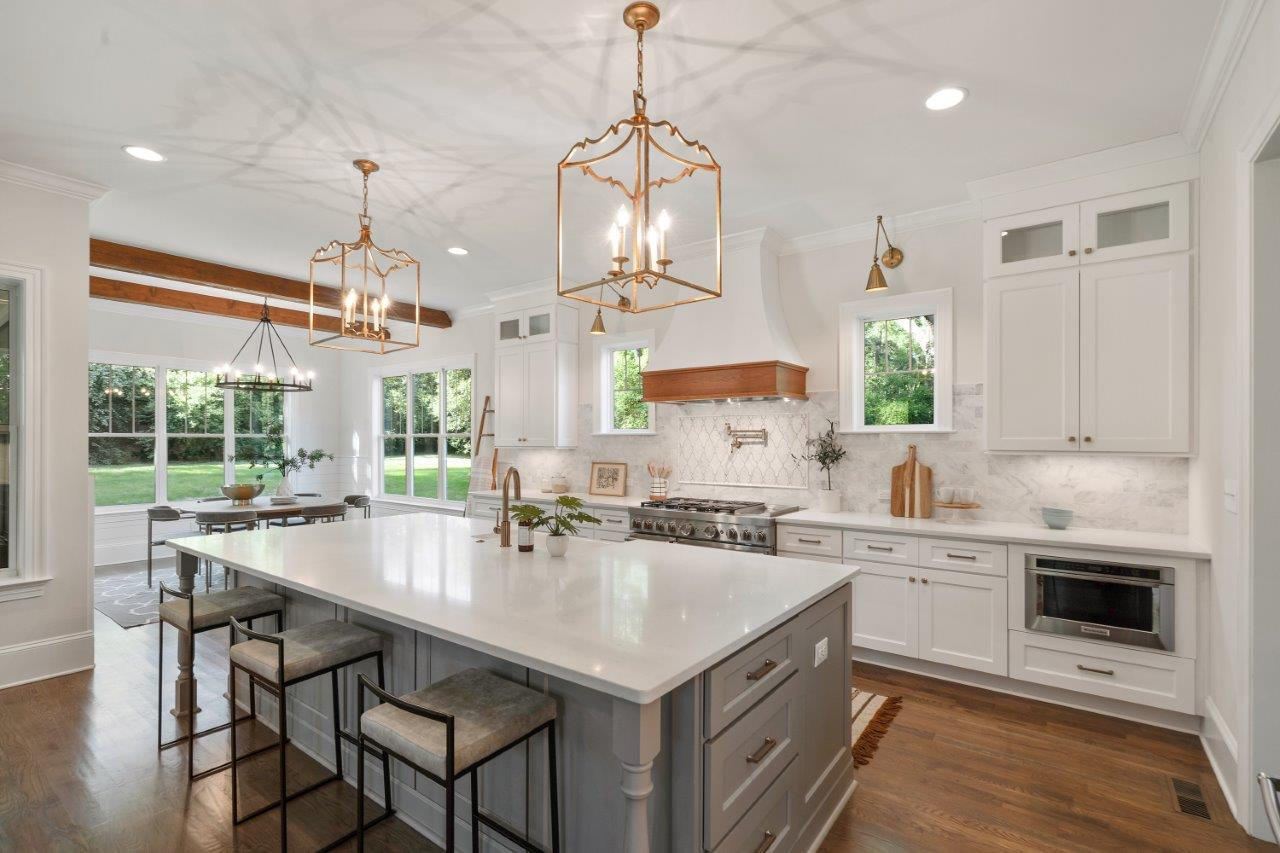 Kitchen with white cabinets white countertops white backsplash gold hardware windows on sides of oven wood floors and open to dining room