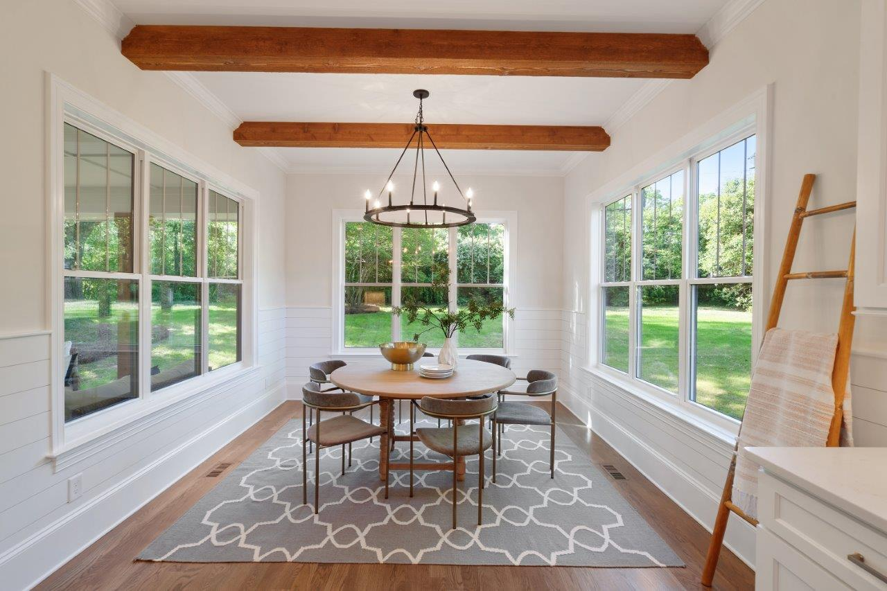 Dining room with white walls with white shiplap on the bottom half of walls wood floors and wood beams on ceiling